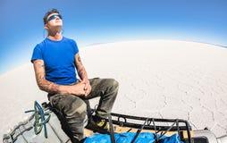 A tomada de solo do viajante do homem novo relaxa a ruptura em Salar de Uyuni Bolivia imagens de stock
