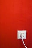 Tomada elétrica na parede vermelha imagem de stock royalty free