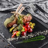 Tomahawk rib beef steak on bone and vegetables with sauce on black shale board over black stone background. Hot Meat Dishes royalty free stock photography