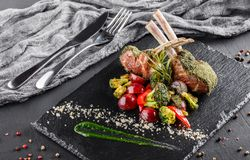 Tomahawk rib beef steak on bone and vegetables with sauce on black shale board over black stone background. Hot Meat Dishes royalty free stock photos