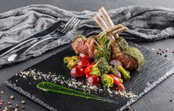 Tomahawk rib beef steak on bone and vegetables with sauce on black shale board over black stone background. Hot Meat Dishes royalty free stock images
