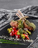 Tomahawk rib beef steak on bone and vegetables with sauce on black shale board over black stone background. Hot Meat Dishes stock photo