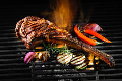 Tomahawk rib beef steak on grill. Tomahawk rib beef steak on hot black grill with flames Stock Photos