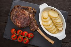 Tomahawk rib steak. With tomato and potato on a slate board stock image