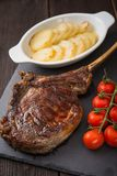 Tomahawk rib steak. With tomato and potato on a slate board stock images
