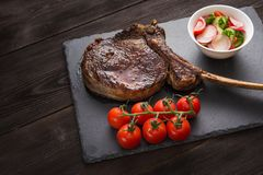 Tomahawk rib steak. With tomato and potato on a slate board royalty free stock image