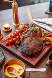 Tomahawk steak with mash potato, baked spinach cheese and gravy sauce. Served with red wine royalty free stock image