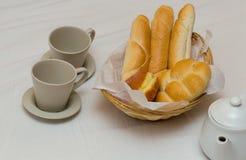 Tomam o café da manhã dois copos um bule com uma cesta do pão fresco com os anéis de espuma franceses dos baguettes fotografia de stock royalty free