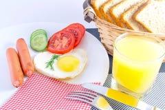 Tomam o café da manhã em um ovo frito da tabela no as salsichas fritadas coração-dadas forma, vegetais cortados frescos, suco, br Fotografia de Stock Royalty Free