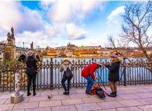 Toman los turistas la foto del castillo de Praga, cerca del puente de Charles sobre el río de Moldava imagenes de archivo