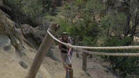 Toman para una verja de la cuerda y sube el turista activo de la mujer para arriba la colina almacen de metraje de vídeo