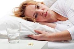 Tomando comprimidos - mulher que coloca na cama Fotografia de Stock