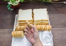 Tomando a cookie à disposição com fundo do pão Fotografia de Stock Royalty Free
