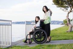Tomando da irmã na cadeira de rodas pela praia Imagens de Stock
