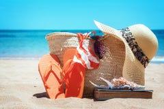 Tomando el sol los accesorios en la playa arenosa en paja empaquetan Imagen de archivo libre de regalías