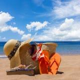 Tomando el sol los accesorios en la playa arenosa en paja empaquetan Fotografía de archivo