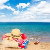 Tomando el sol los accesorios en la playa arenosa en paja empaquetan Imagen de archivo