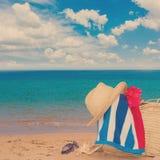 Tomando el sol los accesorios en la playa arenosa en paja empaquetan Imagenes de archivo