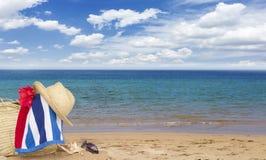Tomando el sol los accesorios en la playa arenosa en paja empaquetan Foto de archivo