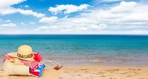 Tomando el sol los accesorios en la playa arenosa en paja empaquetan Fotos de archivo libres de regalías