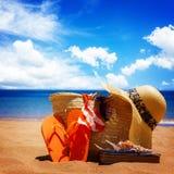 Tomando el sol los accesorios en la playa arenosa en paja empaquetan Imágenes de archivo libres de regalías