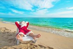 Tomando el sol a Santa Claus que se relaja en el bedstone en la playa - la Navidad Fotos de archivo