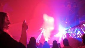 Tomando el vídeo del concierto de rock, baile de la muchacha con las manos para arriba, muchedumbre iluminada por las luces color
