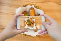 Tomando a foto das asas de galinha quentes e picantes com smartphone Imagens de Stock Royalty Free