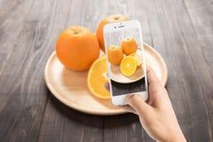 Tomando a foto de laranjas frescas no prato de madeira, frutos frescos no wo Fotos de Stock Royalty Free