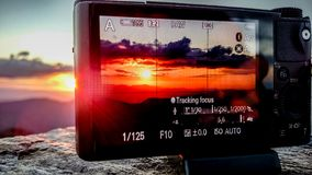 Tomando a foto do por do sol com uma câmera nas montanhas Fotografia de Stock Royalty Free
