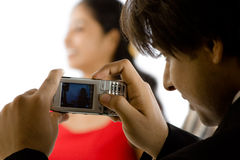 Tomando a fotografia de uma menina com câmera do telemóvel Fotografia de Stock Royalty Free