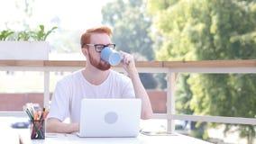 Tomando o sorvo do café quente, bebendo ao sentar-se no escritório exterior, cabelos vermelhos foto de stock royalty free