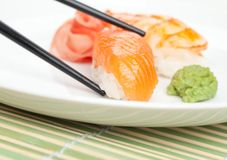 Tomando o sushi da placa branca Fotos de Stock Royalty Free