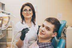 Tomando oral Dentista e paciente masculino na sala dental fotos de stock royalty free
