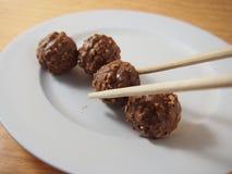 Tomando por hashis, bolas do chocolate de leite foto de stock royalty free