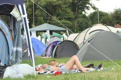 Tomando sol e tomando uma ruptura no festival Imagem de Stock