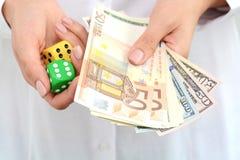 Tomando um risco e ganhando o conceito com um par de dados e de dinheiro Fotografia de Stock