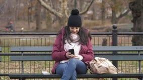 Tomando um selfie ao relaxar em um banco no Central Park vídeos de arquivo