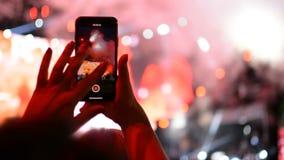 Tomando uma foto com o iPhone do telefone celular durante o concerto do desempenho da música de grupo de rock na fase video estoque