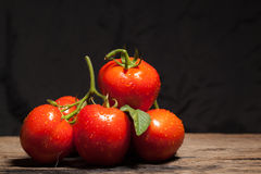 Tomao. Juicy red tomatoes and black background Stock Photo