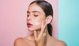 Tomar buen cuidado de su piel Crema de extensi?n de la mujer hermosa en su cara Concepto de la crema de piel Cuidado facial para  fotografía de archivo libre de regalías