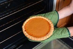 Tomar el pastel de calabaza del horno Foto de archivo