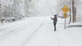 Tomar el selfie en la nieve con la placa de calle detrás de ella fotos de archivo libres de regalías