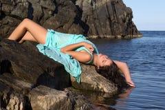 Tomar el sol a la mujer en roca de la playa Imagenes de archivo