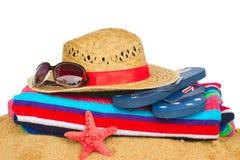 Tomar el sol los accesorios con la toalla en la arena Foto de archivo libre de regalías
