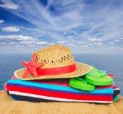 Tomar el sol los accesorios y el sombrero de paja en la arena Foto de archivo