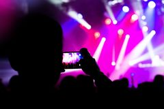 Tomar a foto el teléfono móvil video siluetea a la muchedumbre Imágenes de archivo libres de regalías