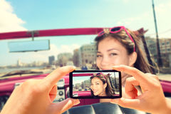 Tomar imágenes con el teléfono elegante de la mujer en coche imagen de archivo