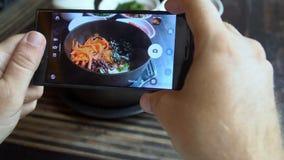 Tomar la foto de la comida del Bibimbap coreano tradicional del plato sirvió junto con pequeños acompañamientos clled banchan en  metrajes