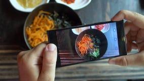 Tomar la foto de la comida del Bibimbap coreano tradicional del plato sirvió junto con pequeños acompañamientos clled banchan en  almacen de video